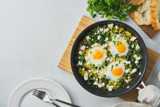 Shakshouka verde com ovos, espinafre, leite de ovelha salgado, aipo, pimenta e ciabatta