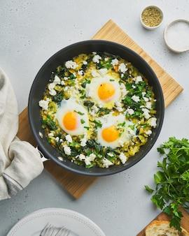 Shakshouka verde com ovos, espinafre, queijo de ovelha salgado, aipo e pimenta na frigideira