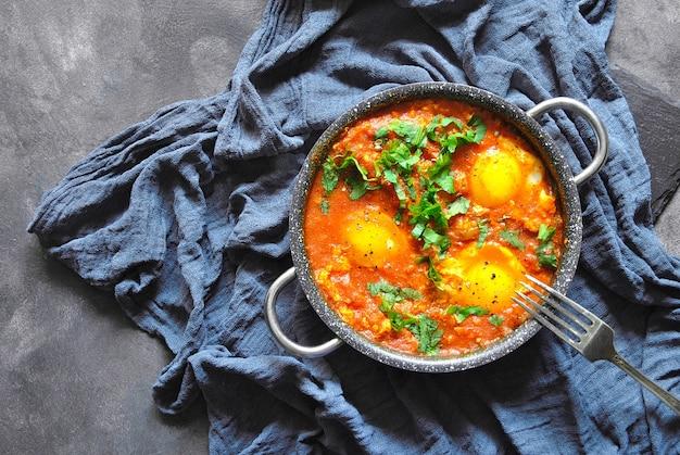 Shakshuka na panela sobre uma superfície rústica cinza. pratos tradicionais do oriente médio. ovos fritos com legumes. espaço para texto. vista do topo.