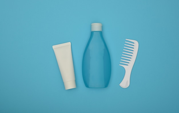 Shampoo, condicionador e pente de cabelo sobre azul