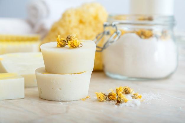 Shampoo em barra sólida e muitas barras redondas de sabonete artesanal com flores de calêndula seca de ervas. produtos de banho de spa com aroma de sal, toalha natural na mesa de mármore. produtos cosméticos de beleza para relaxamento corporal.