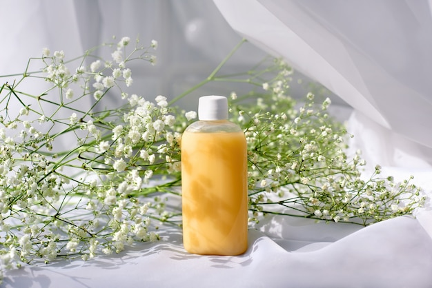 Shampoo, gel ou loção em frasco de plástico transparente com tampa em fundo branco com flores da primavera