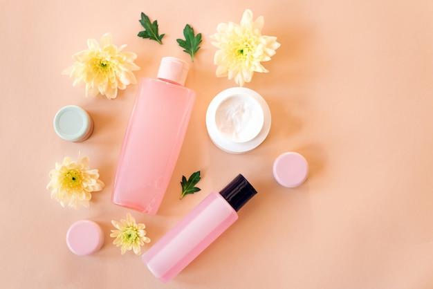 Shampoo, gel, sabão, creme e recipientes para cassetes com flores amarelas em bege