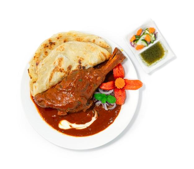 Shank de cordeiro assado masala curry servido roti é uma cebola saborosa, tomate, castanha de caju, molho, condimento e iogurte que tem sido lento.
