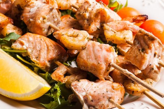 Shashlik de frutos do mar - fatias de salmão e camarão em espetos de madeira