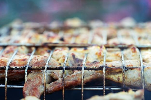 Shashlik de porco e frango é grelhado na grelha ao ar livre em casa no verão.
