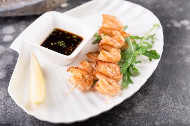 Shashlik de salmão grelhado com limão e molho em um prato branco em um restaurante.