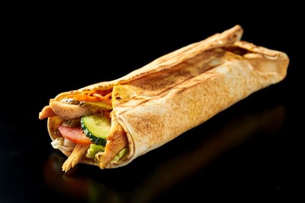 Shawarma apetitoso com frango, pepino, cenoura e tomate no pão pita. superfície preta. isolado. close up, foco seletivo Foto Premium