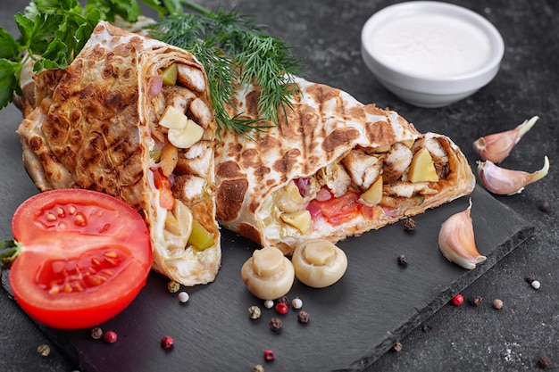 Shawarma com carne de frango, com molho, cebola, picles, tomate, alho, ervas e cogumelos champignon, na ardósia, contra um fundo escuro de concreto