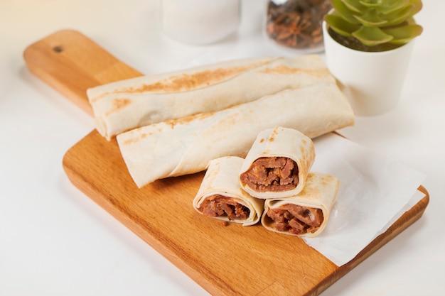 Shawarma com carne e maionese em uma tábua de madeira