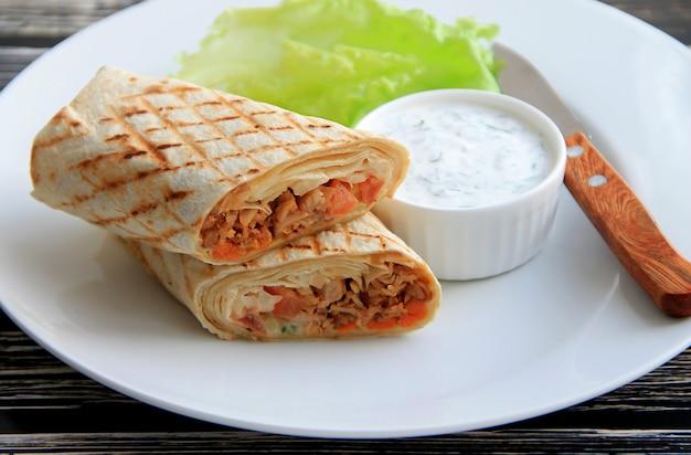 Shawarma com frango, legumes e ervas em um prato branco ao lado do molho e faca