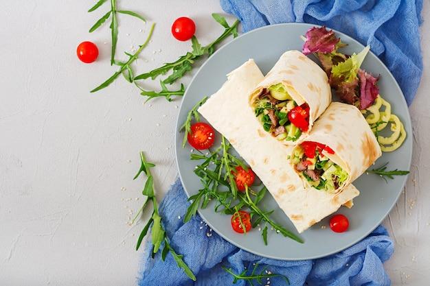 Shawarma de carne suculenta, alface, tomate, pepino, pimentão e cebola no pão pita.