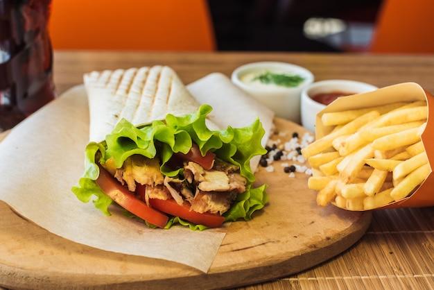Shawarma e batatas fritas em uma placa de madeira em um restaurante. tortilla com uma bebida em um café.