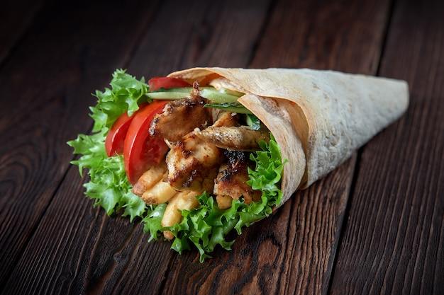 Shawarma enrolado em lavash com carne grelhada e legumes em fundo de madeira
