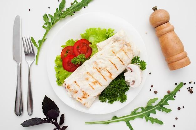 Shawarma no prato com talheres e caixa de pimenta
