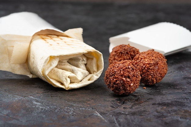 Shawarma oriental tradicional com costeletas de falafel fritas em um fundo preto. lanches saudáveis ou almoço para viagem. conceito de eco-embalagens para materiais recicláveis. copie o espaço