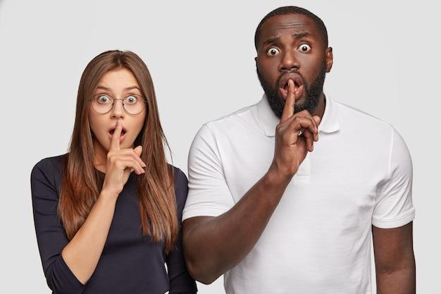 Shh. casal interracial fazendo gesto de silêncio