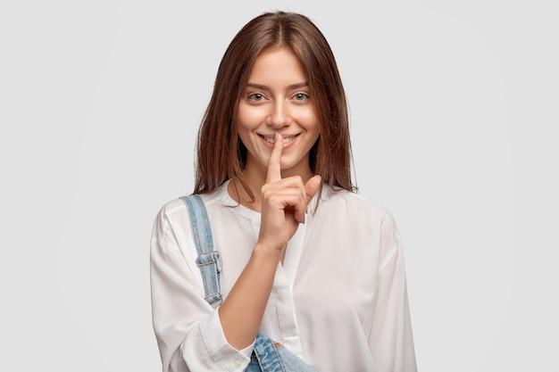 Shh, é privacidade! mulher bonita de cabelo escuro com sorriso encantador, mantém o dedo indicador sobre a boca