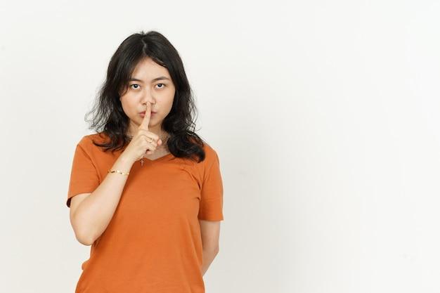 Shh, fique quieto com a linda mulher asiática usando uma camiseta laranja isolada no fundo branco