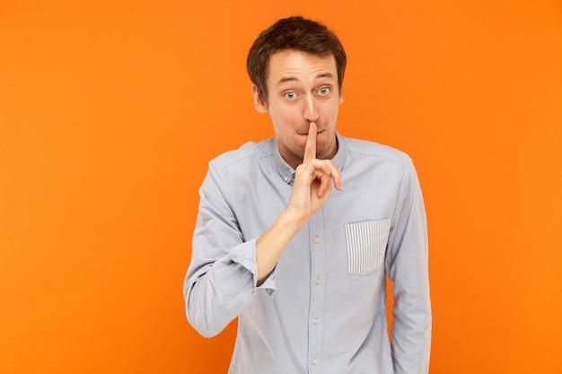 Shh, seu empresário secreto segurando o dedo perto da boca e olhando para a câmera com grandes olhos chocados