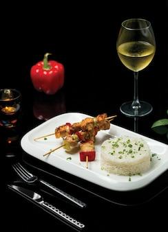 Shish kebab com filé de frango e guarnição de arroz acompanhado por um copo de vinho branco