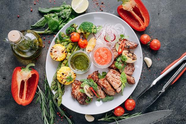 Shish kebab e legumes grelhados e servidos em um prato branco.