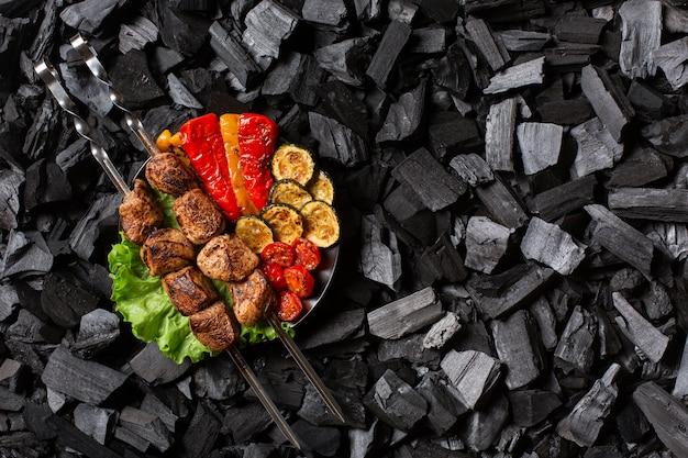 Shish kebab em espetos e vegetais grelhados