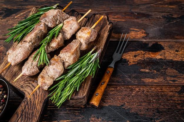 Shish kebab no espeto com ervas em uma placa de madeira. fundo de madeira escuro. vista do topo. copie o espaço.