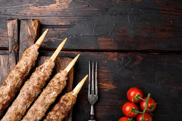 Shish kebab no palito, de carne de carneiro de terra moída definida, a serviço de mesa, no fundo da mesa de madeira escura velha, vista de cima plana lay, com espaço de cópia para o texto