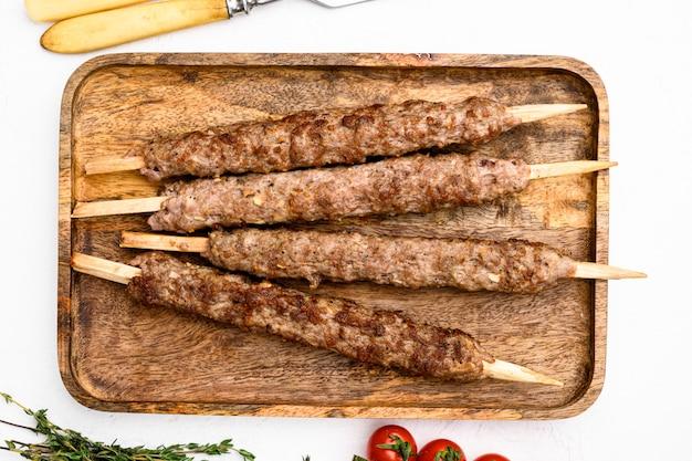 Shish kebab no palito, de carne de carneiro de terra moída definida, no fundo da mesa de pedra branca, vista de cima plano plano