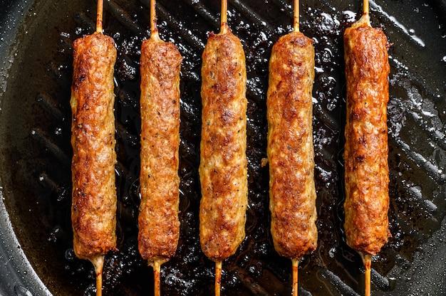 Shish kebab no palito, de carne moída. lula kebab. fundo branco.