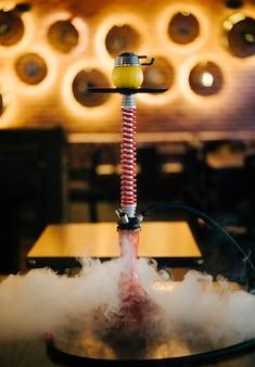 Shisha de fumo árabe com vapor em um restaurante.