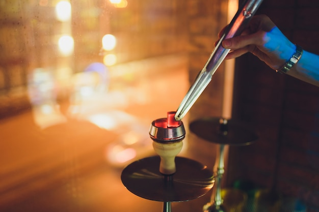 Shisha tigela com tabaco artesanal e bobina vermelha com fumaça de cachimbo de água.