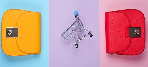 Shopaholic conceito minimalista. dois sacos, mini carrinho de compras. vista do topo