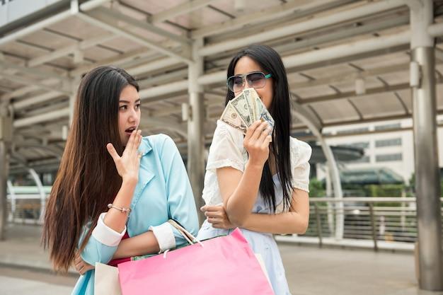 Shopaholic mulher mostrando dinheiro para um amigo