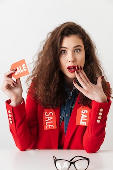 Shopping mulher segurando placa de venda enquanto está sentado na mesa