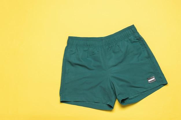 Shorts de praia na moda masculina em um fundo amarelo. roupas populares de verão.