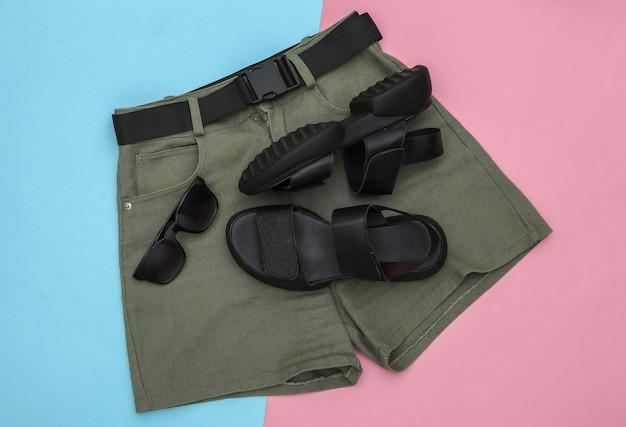 Shorts e sandálias de couro, óculos de sol em fundo rosa pastel azul. roupas e acessórios femininos. vista do topo. postura plana