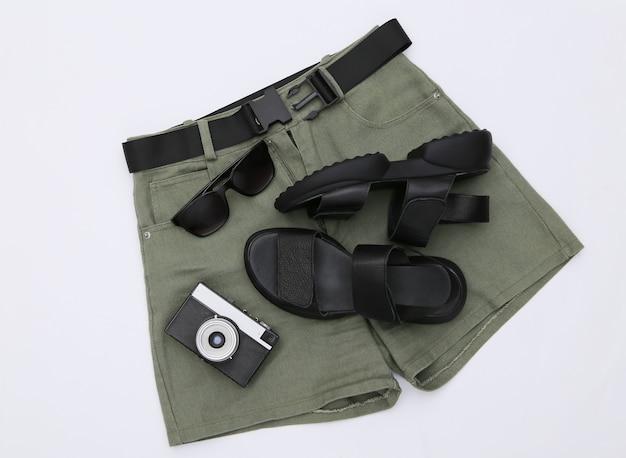 Shorts e sandálias de couro, óculos escuros e câmera em um fundo branco. roupas femininas e acessórios de viagem. vista do topo. postura plana