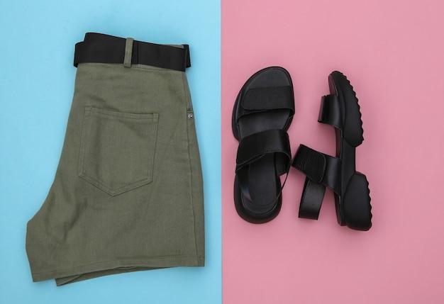 Shorts jeans e sandálias de couro em fundo rosa azul pastel. roupas e acessórios femininos. vista do topo. postura plana