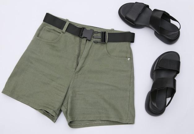 Shorts jeans e sandálias de couro em um fundo branco. roupas e acessórios femininos. vista do topo. postura plana