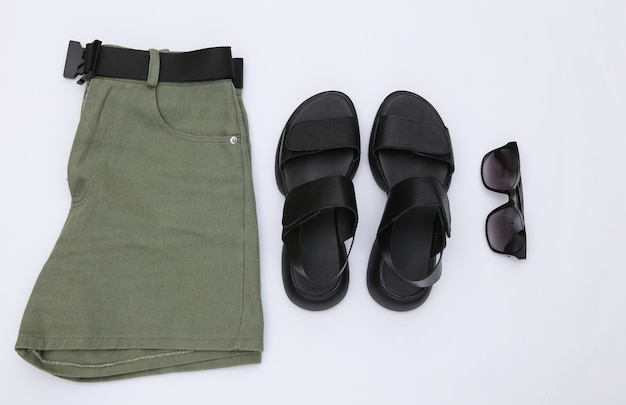 Shorts jeans e sandálias de couro, óculos de sol sobre um fundo branco. roupas e acessórios femininos. vista do topo. postura plana