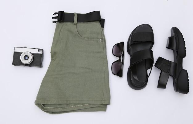Shorts jeans e sandálias de couro, óculos escuros e câmera em um fundo branco. roupas femininas e acessórios de viagem. vista do topo. postura plana