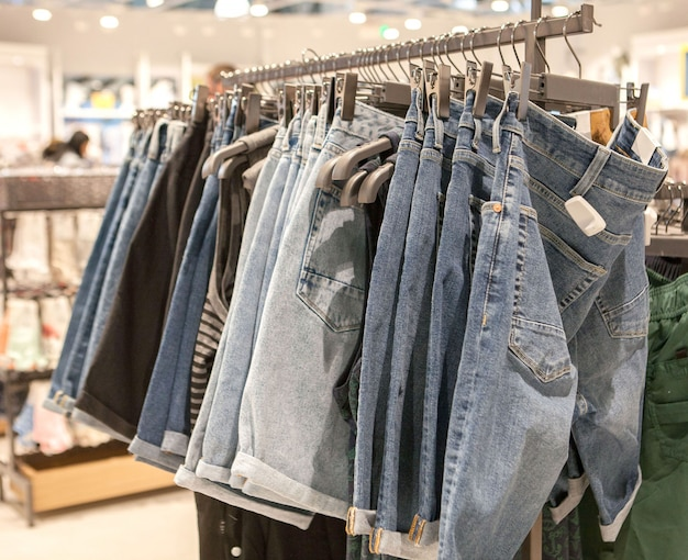 Shorts jeans na prateleira da loja. roupas da moda nas prateleiras da loja. jeans pendurados nos coletes da loja de moda.