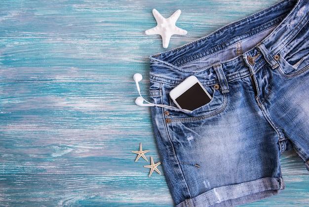 Shorts jeans, telefone celular, fones de ouvido, conchas