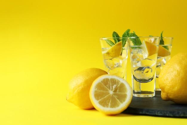 Shots com rodelas de limão e hortelã na bandeja na superfície amarela