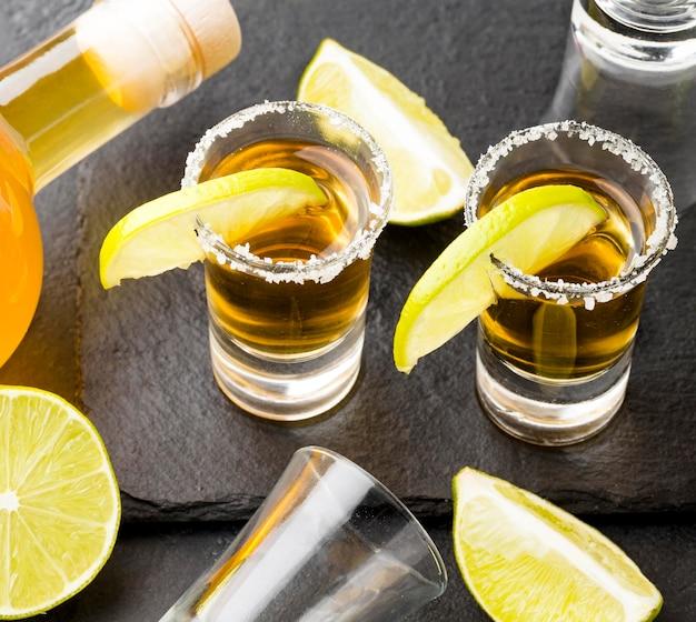 Shots de tequila dourada de alto ângulo e limão com sal e garrafa
