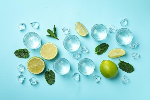 Shots, rodelas de limão, hortelã e cubos de gelo em azul, vista superior