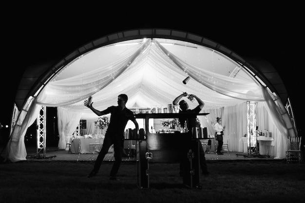 Show de bartenders no fundo de uma barraca de banquete em silhuetas