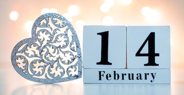 Show de calendário de madeira de 14 de fevereiro com coração de madeira. conceito de dia dos namorados.